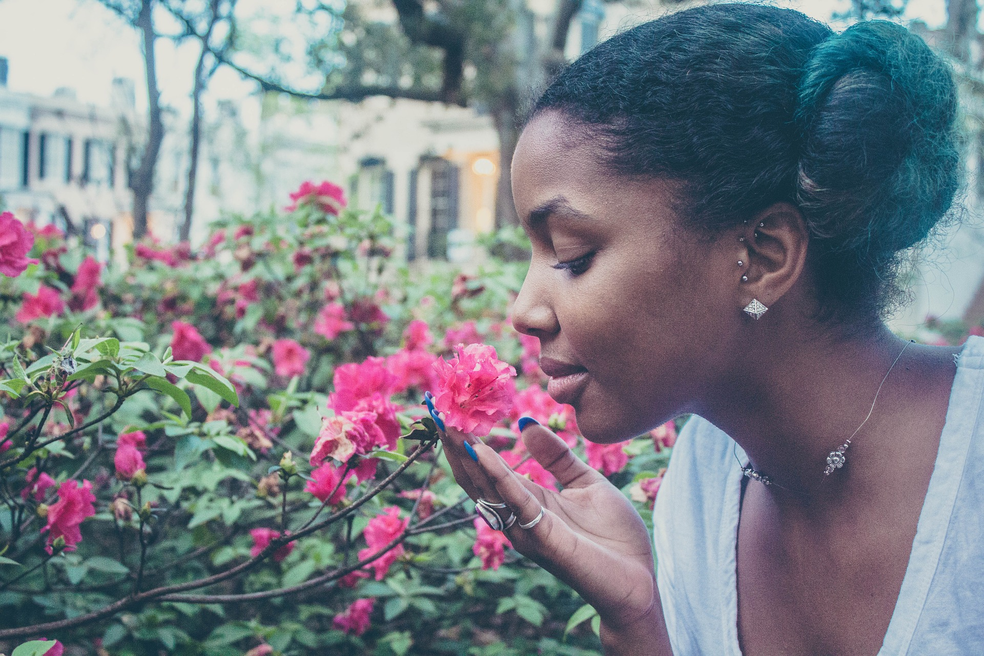 Young brown woman smelling a flower