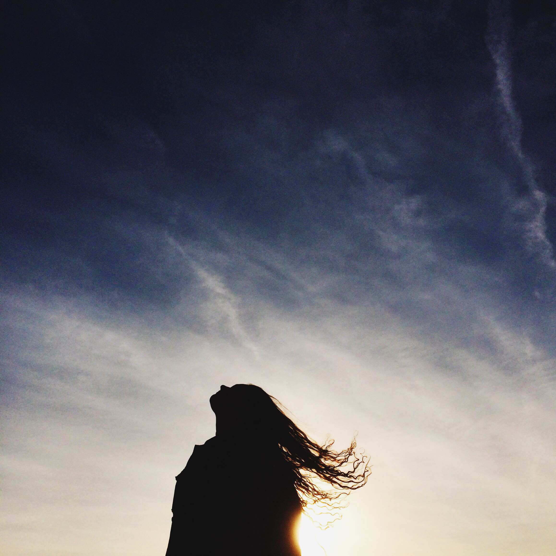 Long-haired woman looking up into the sky