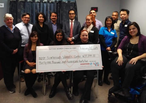 Group of Scarborough Women's Staff and Shoppers Drug Mart staff holding a donation cheque.