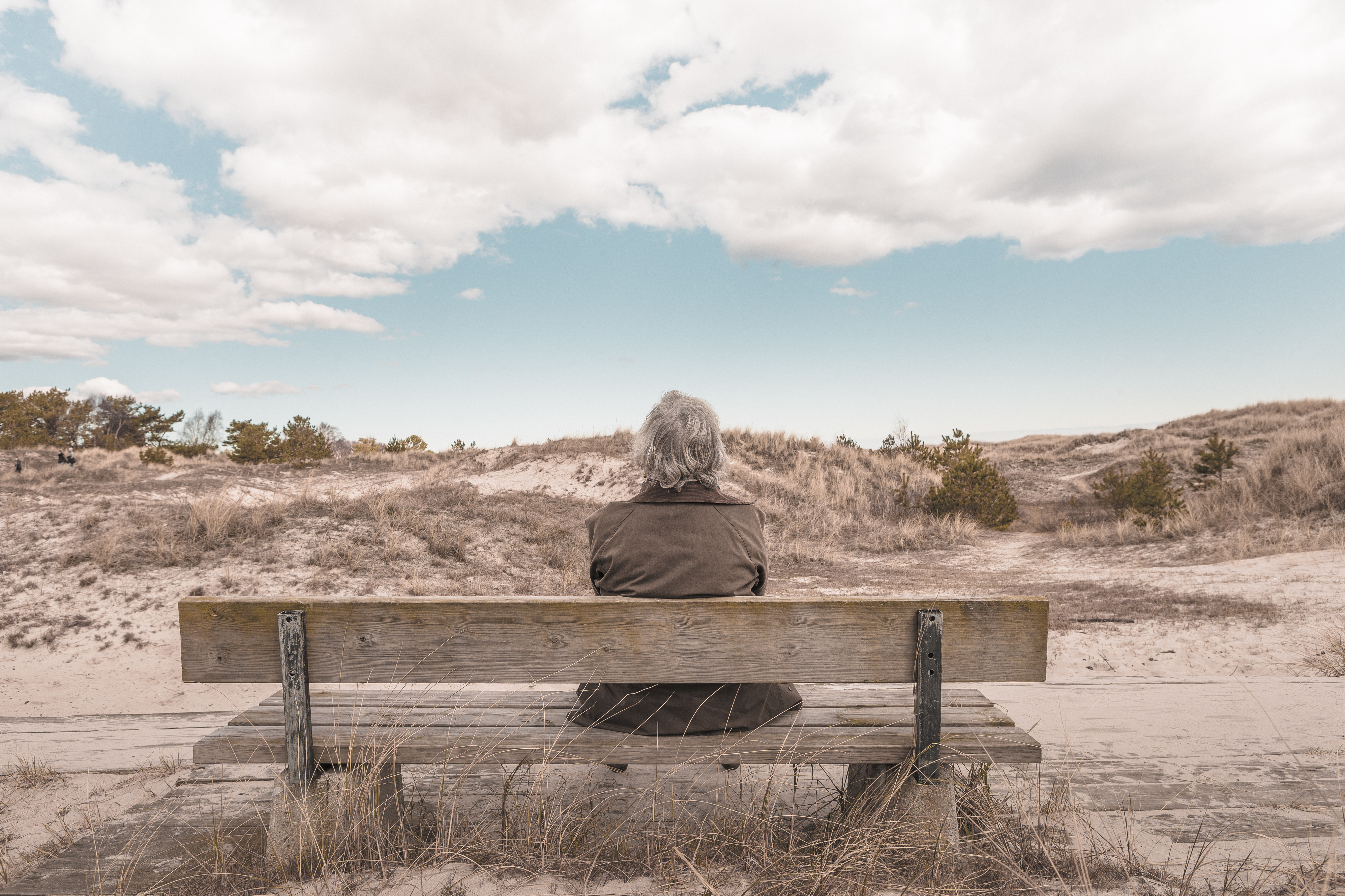 Grey haired woman sitting on bench looking at a sandy hill