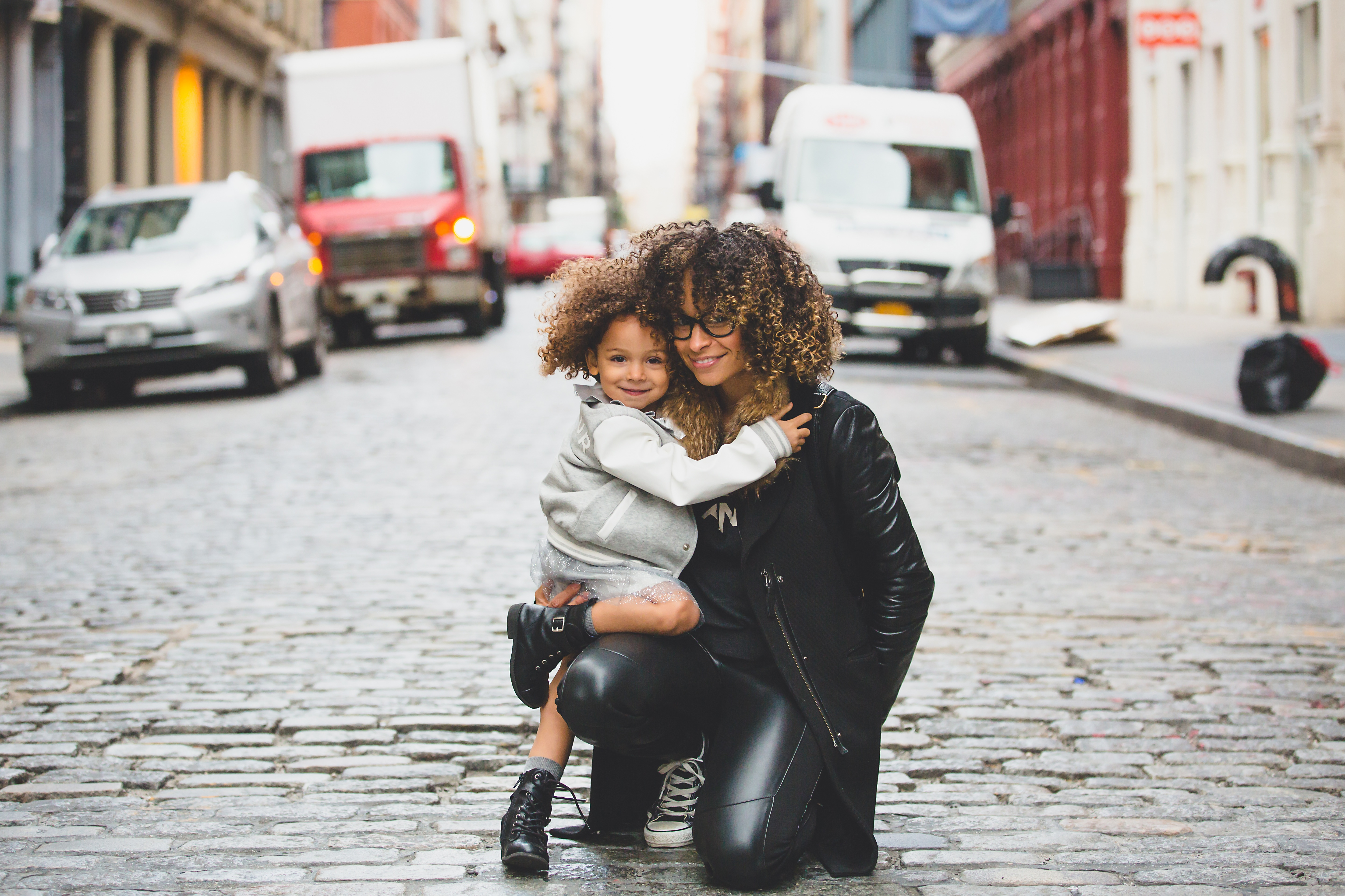 Photo of black woman and child on cobbled street
